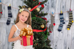 Teenage girl holding Christmas present in front of New Year tree Stock Images