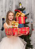 Teenage girl holding Christmas presents in front of New Year tree stock photography