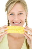 Teenage girl holding corn on cob and smiling Royalty Free Stock Images