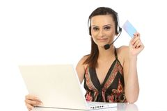 Teenage girl holding credit card and calling. Teenage girl  using laptop, holding credit card and making an order via phone Royalty Free Stock Image