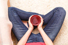 Teenage girl holding cup of tea sittng on floor Royalty Free Stock Images