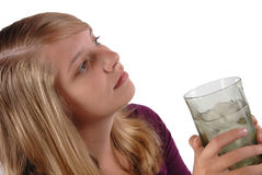 Teenage girl holding glass ice water looking away Royalty Free Stock Photos