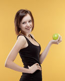 Teenage girl holding a green apple smiling Royalty Free Stock Image