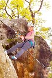 Teenage girl holding harness rope during downclimb stock photos
