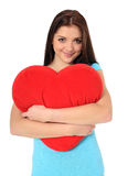 Teenage girl holding heart-shaped pillow Stock Images