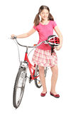 Teenage girl holding a helmet and pushing a bike Royalty Free Stock Photography