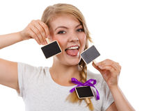 Teenage girl holding little school blackboards. School, education, learning concept. Teenage girl holding little school blackboards and ticking her tongue out stock photo