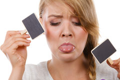 Teenage girl holding little school blackboards. School, education, learning concept. Teenage girl holding little school blackboards and ticking her tongue out stock photography