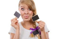 Teenage girl holding little school blackboards. School, education, learning concept. Teenage girl holding little school blackboards and ticking her tongue out stock images