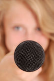 Teenage girl holding a microphone in front Stock Photography