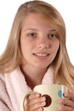 Teenage girl holding morning cup hot chocolate. Teenage girl wearing a housecoat holding her hot chocolate in studio isolated on white background Royalty Free Stock Photo
