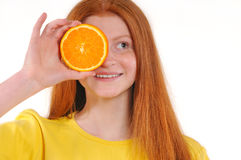 Teenage girl holding piece of orange in front of her eye Stock Images