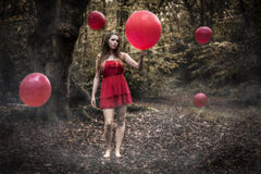 Teenage Girl Holding Red Balloon In Misty Forest With Floating B. Portrait of a beautiful teenage witch girl with long dark blond hair wearing a short red dress Royalty Free Stock Images