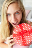 Teenage girl holding red polka dot gift box. Smiling at camera from high viewpoint Stock Photography