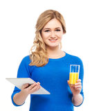 Teenage girl holding a tablet and a glass of orange juice Royalty Free Stock Photos