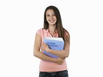 Teenage girl holding textbook, smiling, portrait, cut out Royalty Free Stock Image