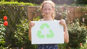Teenage girl holding up an image of the recycling symbol. In a garden stock video