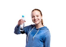 Teenage girl holding water bottle. Studio shot, isolated. Teenage girl in blue sweatshirt, wearing phone armband, holding water bottle, smiling. Beautiful young Royalty Free Stock Photography