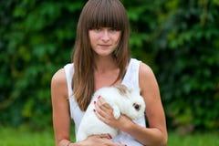 Teenage girl holding white rabbit. In the yard Stock Photo
