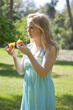 Teenage Girl Holding Wild Orange. Teenage girl, white, holding a wild orange she has picked from a nearby tree.  She has peeled it and broken it in two pieces Royalty Free Stock Image