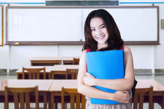Teenage girl holds folder in the classroom Royalty Free Stock Photos