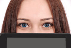 Teenage girl holds in front of face tablet computer stock image