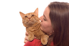 Teenage girl holds orange tabby cat. A teenage girl holds her pet, an orange tabby with orange eyes, isolated against white background Royalty Free Stock Photo
