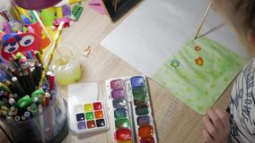 Teenage girl at home is engaged in creativity, draws watercolor at a table in room. Child drawing top view. Artwork. Workplace with creative accessories stock video