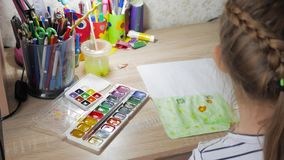 Teenage girl at home is engaged in creativity, draws watercolor at a table in room. Child drawing top view. Artwork. Workplace with creative accessories stock video footage