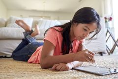 Teenage girl at home lying on the floor in the living room using tablet computer and stylus, low angle, close up royalty free stock image
