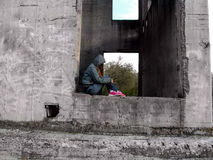 A teenage girl in a hood without a face sits in a rectangular hole of a concrete wall. The concept of teenage problems, a homeless child stock photo