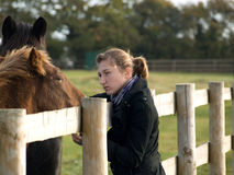 Teenage girl with a horse in a field Royalty Free Stock Photography