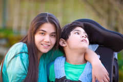 Teenage girl hugging disabled brother in wheelchair outdoors Stock Image