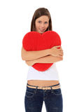 Teenage girl hugging heart-shaped pillow Stock Photo