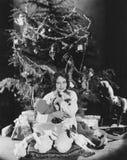 Teenage girl hugging stuffed animals under Christmas tree Royalty Free Stock Images