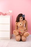 Teenage girl hugging teddy bear in pink room. Pretty teenage girl kneeling on floor, hugging teddy bear in pink room Royalty Free Stock Images