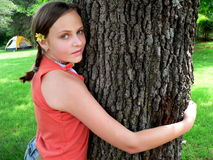 Teenage girl hugging tree. Teenage girl in orange tank with yellow flower in hair hugging tree with a tent in the background Stock Photography