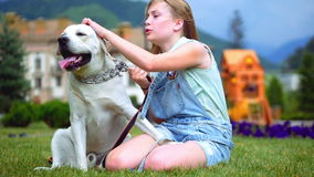 A teenage girl hugs her dog in the park. The dog licks and kisses the girl.. A teenage girl is playing with her favorite stock footage