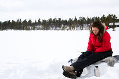 Teenage girl ice fishing. Teenage girl out on a snow covered lake to ice fish Stock Image