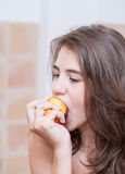 Teenage Girl In Orange T-shirt Eating A Peach Royalty Free Stock Photo