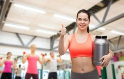 Teenage girl with jar of protein showing thumbs up Royalty Free Stock Photo