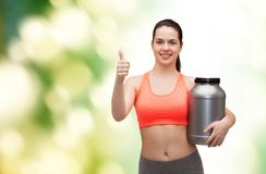 Teenage girl with jar of protein showing thumbs up Stock Photos
