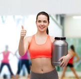 Teenage girl with jar of protein showing thumbs up Stock Photography