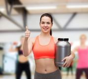 Teenage girl with jar of protein showing thumbs up Stock Images