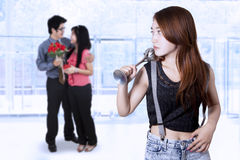 Teenage girl jealous to young couple royalty free stock photo