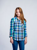 Teenage girl in jeans and checked shirt, studio shot Stock Image