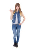 Teenage girl in jeans clothes showing ok sign isolated on white Stock Photography