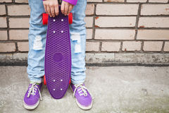 Teenage girl in jeans and gumshoes holds skateboard Stock Photos