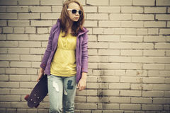 Teenage girl in jeans and sunglasses holds skateboard Royalty Free Stock Images