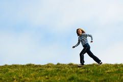 Teenage girl jogging along a hilltop Royalty Free Stock Photo